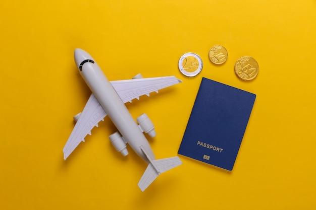 Thema reisen oder auswanderung. flugzeugfigur, reisepass mit münzen auf gelb