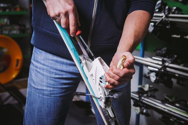Thema tinktur und reparatur skiausrüstung ski. nahaufnahme der hand eines kaukasischen mannes verwenden sie ein handgehaltenes schraubendreherwerkzeug, um die bindungen für skischuhe in der werkstatt zu optimieren.