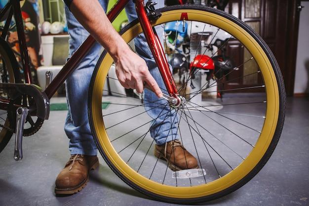 Themenreparaturfahrräder. nahaufnahme der hand eines kaukasischen mannes verwenden sie ein handwerkzeug fahrradwerkzeuge hub cone wrench, um quick releases und steckachsen auf einem roten fahrrad einzustellen und zu installieren.
