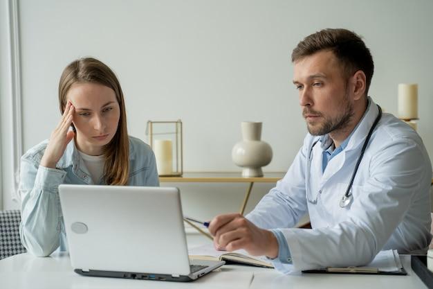 Therapeut arzt mann spricht mit patient erwachsenen mann im weißen kittel spricht mit patientin in der arztpraxis