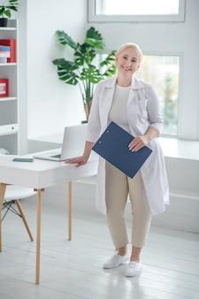Therapeut. blonder arzt in einem weißen gewand, das im büro steht