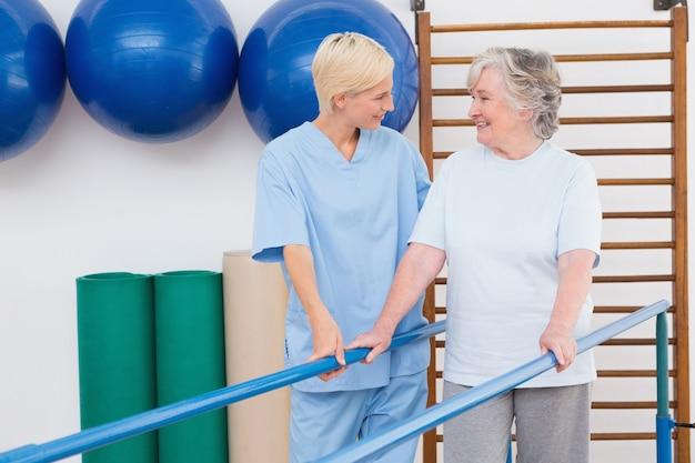 Therapeut, der älterer frau hilft, mit barren zu gehen