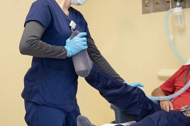 Therapeut, der das bein des männlichen patienten hält