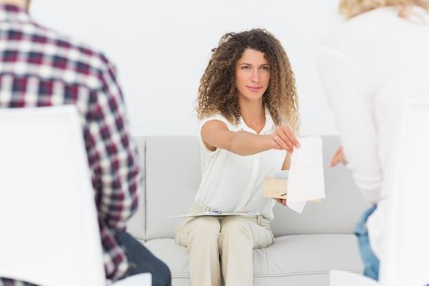Therapeut, der der frau bei der paartherapie ein gewebe übergibt