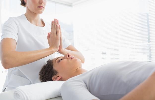Therapeut, der der frau reiki-behandlung gibt