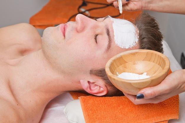 Therapeut, der eine gesichtsmaske an einem schönen jungen mann in einem badekurort anwendet