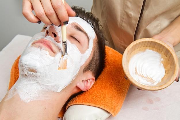 Therapeut, der eine gesichtsmaske an einem schönen jungen mann in einem badekurort unter verwendung eines kosmetikpinsels anwendet