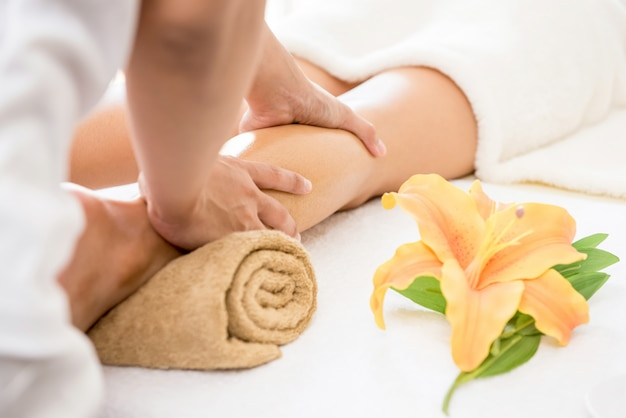 Therapeut, der einer frau im badekurort entspannende thailändische ölbein-massagebehandlung gibt