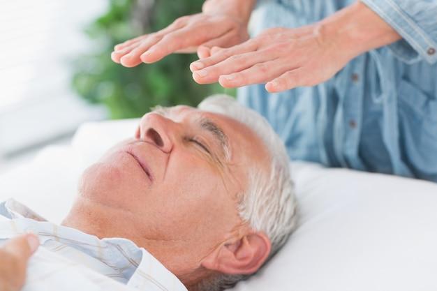Therapeut, der reiki über älterem mann durchführt