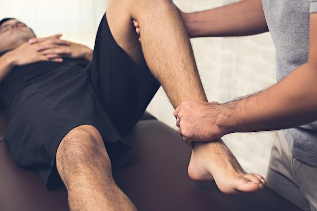 Therapeut, der verletztes bein des männlichen patienten des athleten in der klinik behandelt