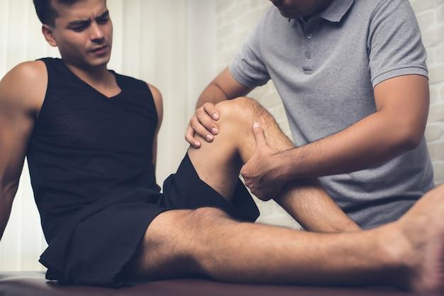 Therapeut, der verletztes knie des männlichen patienten des athleten in der klinik behandelt