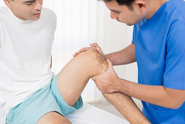 Therapeut, der verletztes knie des männlichen patienten im krankenhaus behandelt
