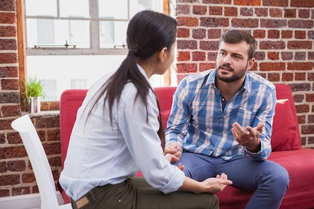 Therapeut, der zu ihrem patienten auf couch im büro hört