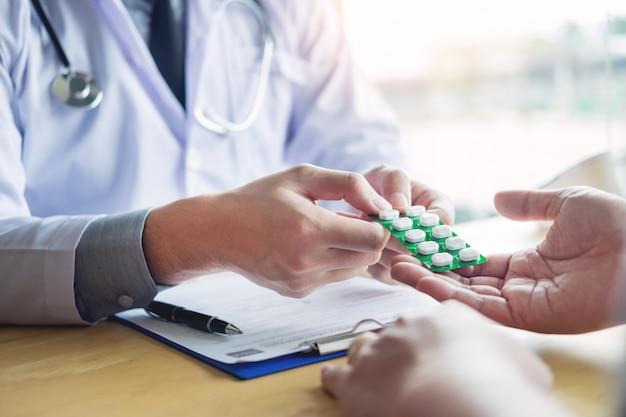 Therapeut, der zum geduldigen männlichen patienten über die pillen schreiben sein medizinisches verschreibungspflichtiges medikament in das büro sich berät.