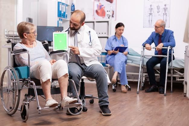 Therapeut hält tablet-pc mit grünem bildschirm während der therapie in der hand