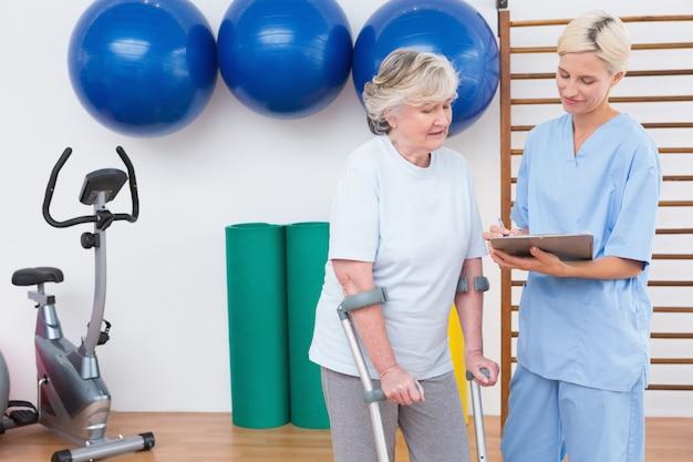 Therapeut und ältere frau, die klemmbrett betrachten