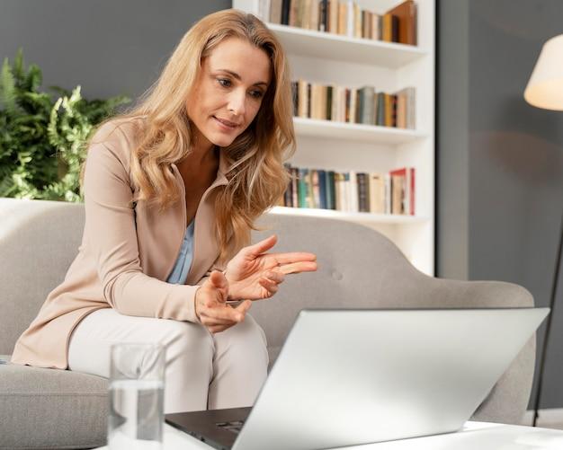 Therapeutin der mittleren schussfrau, die laptop betrachtet