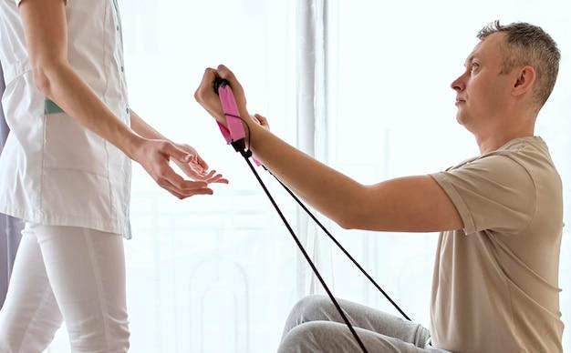 Therapeutin, die sich einer physiotherapie mit einem männlichen patienten unterzieht