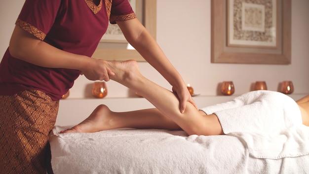 Therapeutin gibt eine entspannende fußmassage. entspannen sie nach einem anstrengenden tag im spa
