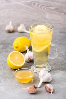 Therapeutisches getränk aus zitrone, honig und knoblauch in einem glas auf dem tisch.
