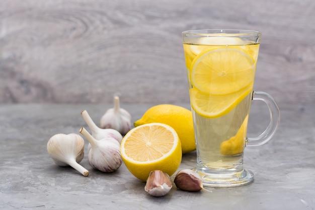 Therapeutisches getränk aus zitrone und knoblauch in einem glas auf dem tisch.