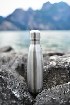 Thermo glänzende stahlflasche für wasser auf dem hintergrund von klarem wasser eines sees