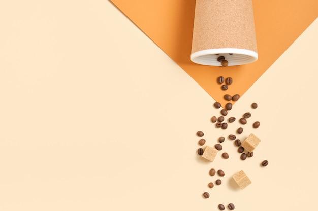 Thermobecher, verstreute kaffeebohnen und braune rohrzuckerwürfel auf braunem und beigem geometrischem hintergrund draufsicht kopieren raum