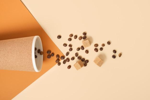 Thermobecher, verstreute kaffeebohnen und braune rohrzuckerwürfel auf braunem und beigem geometrischem hintergrundkopierraum