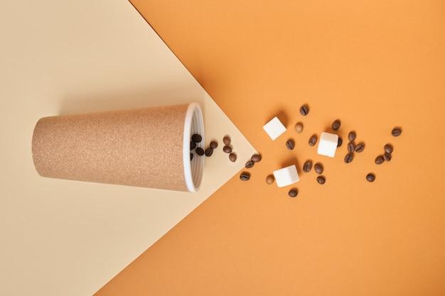Thermobecher, verstreute kaffeekörner und weiße zuckerwürfel auf braunem und beigem geometrischem hintergrundkopierraum
