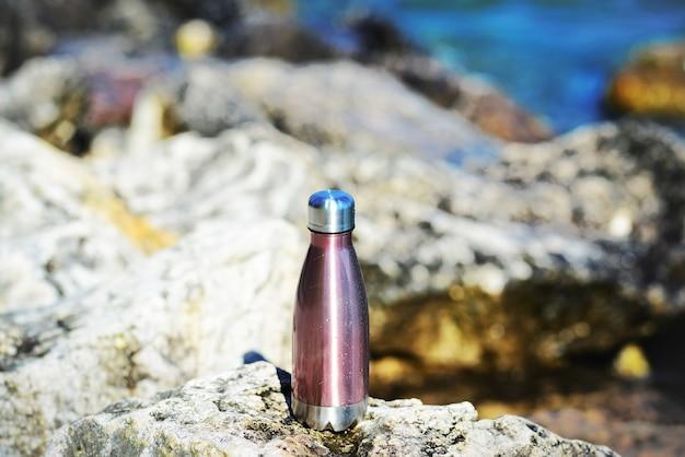 Thermoflasche aus stahl für wasser auf dem hintergrund von klarem wasser eines sees mit türkisfarbenem farbton raumkonzept kopieren umweltfreundliche wasserflasche