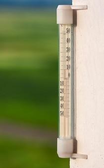 Thermometer celsius, der warme temperatur auf unscharfem grünem hintergrund zeigt