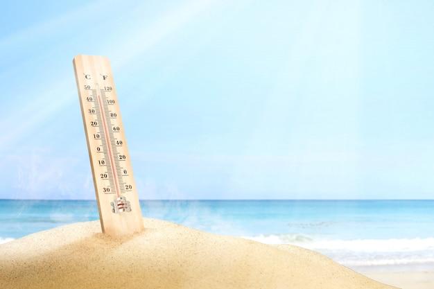 Thermometer, der die temperatur auf dem strand mit einem hintergrund des blauen himmels misst