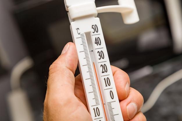 Thermometer in der hand, wärme in der wohnung