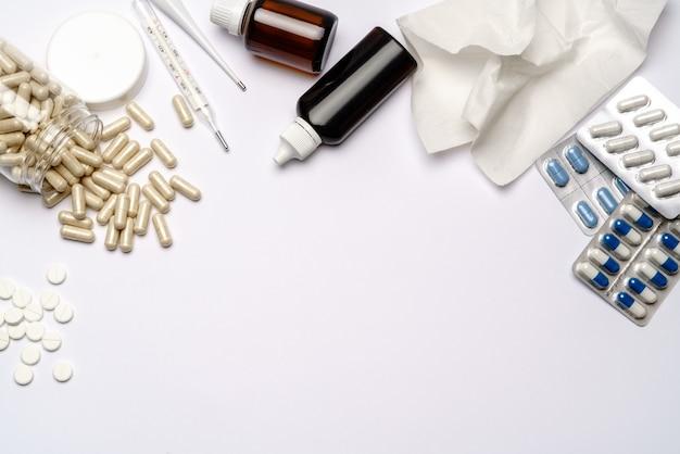 Thermometer, kapseln und tabletten in verpackung auf hellgrauem oder weißem hintergrund - draufsicht flach