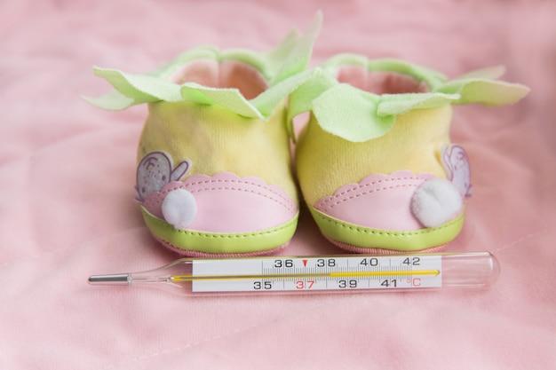 Thermometer mit weichen spielwaren auf rosa hintergrund. gesundes kind