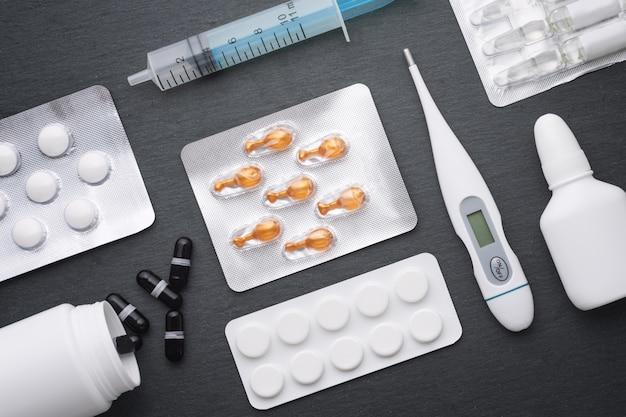 Thermometer, nasentropfen tabletten und ampullen mit medizin auf dunklem schieferbrett. draufsicht, flach liegen. medikamente zur rauchbehandlung und antibiotika, gesundheitskonzept.