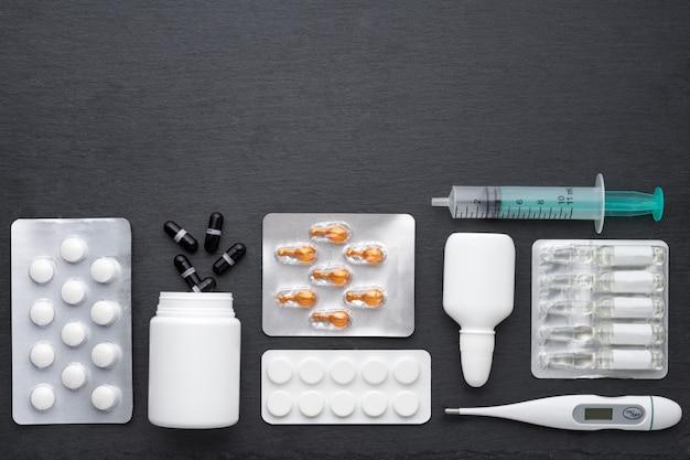Thermometer, nasentropfen tabletten und ampullen mit medizin auf dunklem schieferbrett. draufsicht, flache lage, kopierraum. medikamente zur rauchbehandlung und antibiotika, gesundheitskonzept.