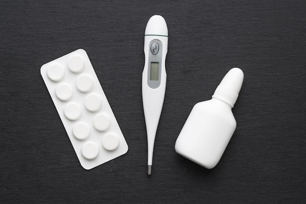 Thermometer, nasentropfen und tabletten auf dunklem schieferbrett. flach liegen. medikamente für die rauchbehandlung, gesundheitskonzept.