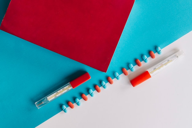 Thermometer; rotes papier; tabletten auf doppeltem hintergrund