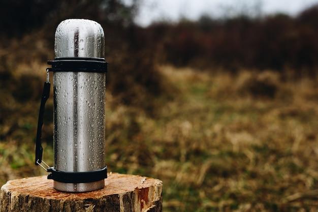 Thermosflasche, die auf einer hölzernen anmeldung den wald steht. platz für text