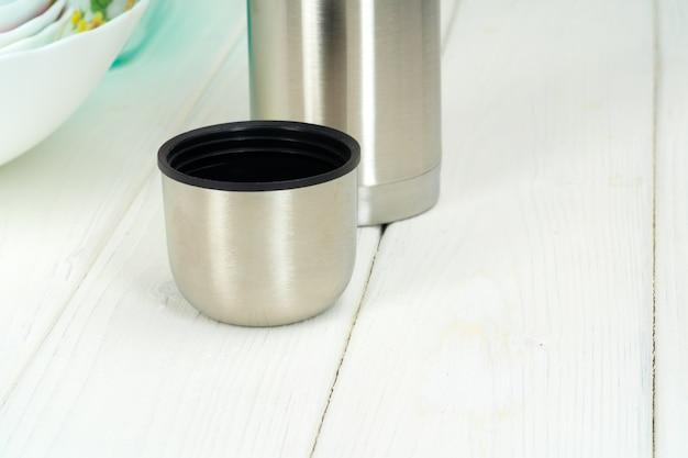 Thermosflasche gegen geschirr in einer küche