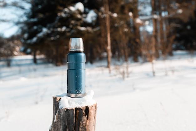 Thermoskanne, die auf einem schneebedeckten baumstumpf in einem winterwald an einem sonnigen tag steht. trekking-konzept, camping
