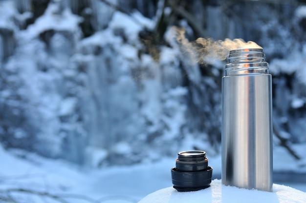 Thermoskanne mit einem heißen getränk am bergwasserfall