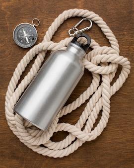 Thermoskanne mit wasser und seil mit kompass gefüllt