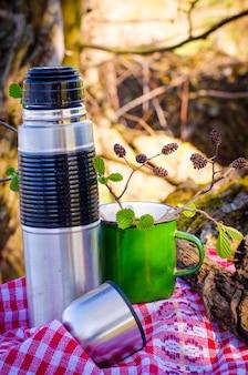 Thermoskanne und eine tasse in der natur verwendet