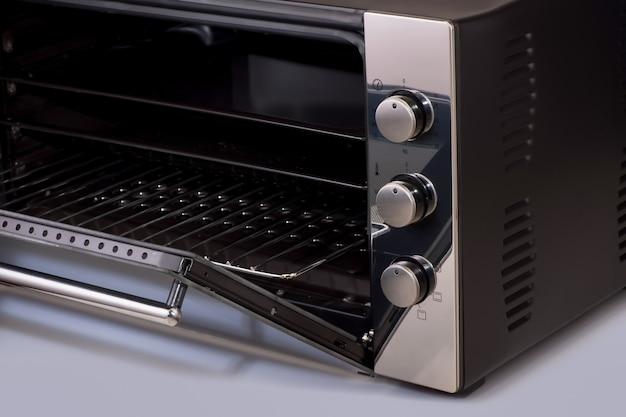 Thermostat und knöpfe an einer modernen mikrowelle, offene backofentür. küchenausstattung