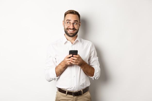 Thouthful hübscher manager, der handy verwendet und über das beantworten der nachricht nachdenkt, die obere linke ecke betrachtet und lächelt und über weißem hintergrund steht.