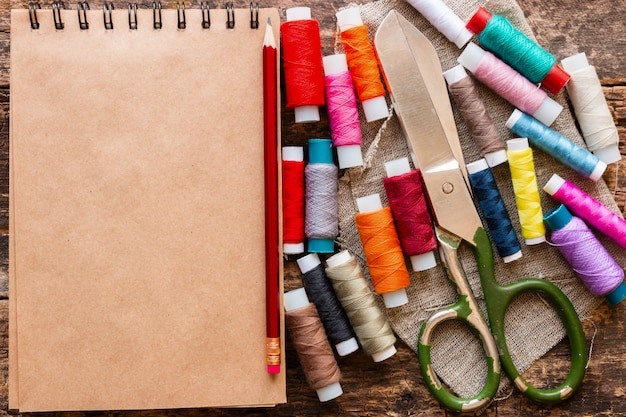 Thread, schere und notizblock auf holz