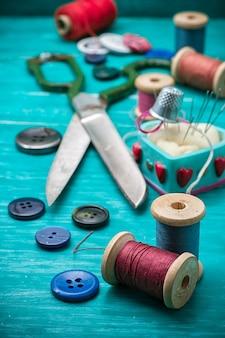 Threadknöpfe für handwerk auf hölzernem hintergrund des türkises.