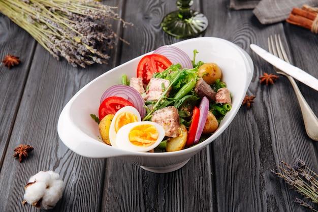 Thunfisch-eier und gemüsesalat auf dem holztisch